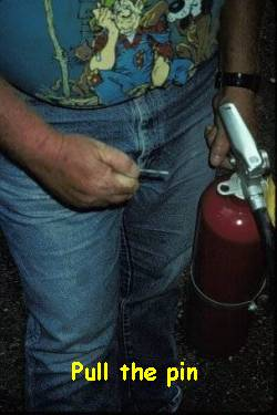 Person pulling extinguisher pin